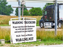 When a truck driver pulls into the Lion's Den parking lot he sees a sign: ...
