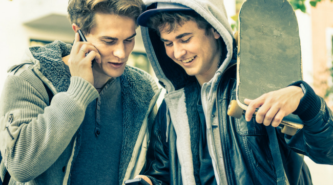 two teen boys on cell phone