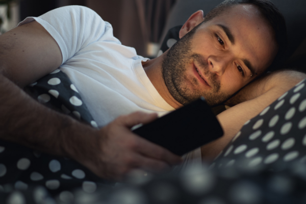 man looking at phone in bed