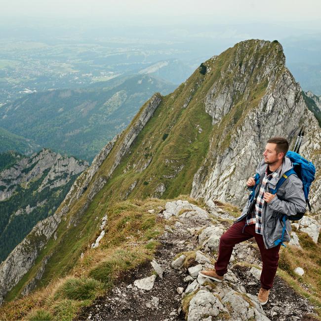pensive man at top of mountain peak