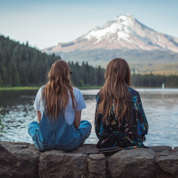 two friends talking by lake