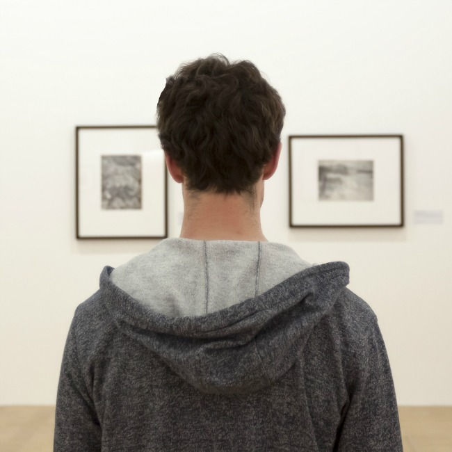 Young adult watching paintings in modern art museum in Paris