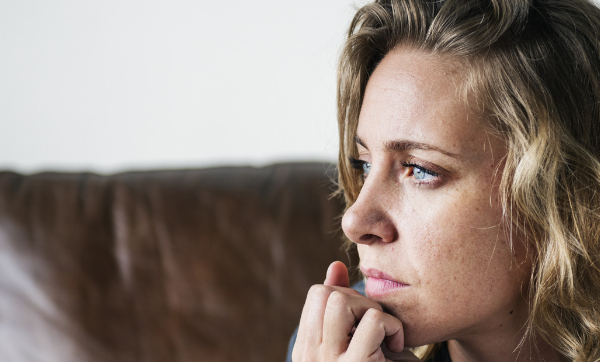 depressed young woman sitting on couch