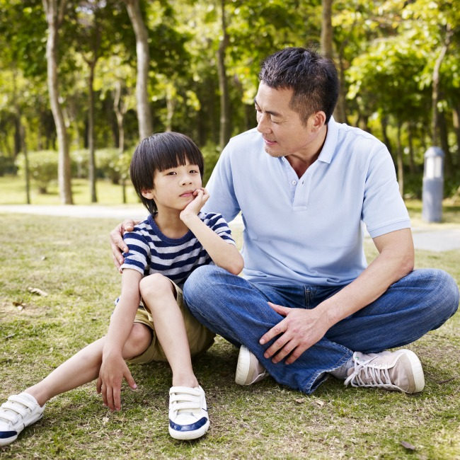 dad and young son talking in park