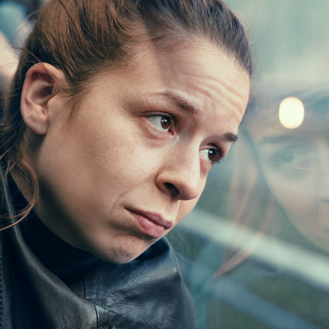 sad woman staring out train window