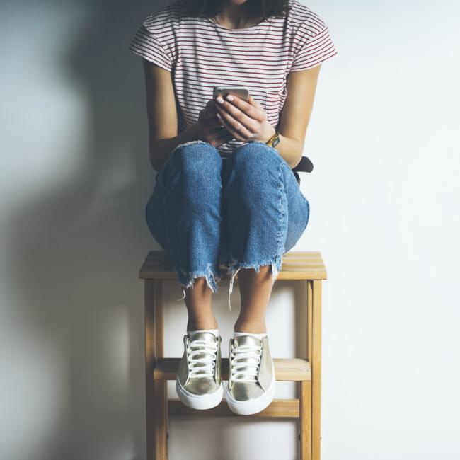 woman sitting on stool watching phone