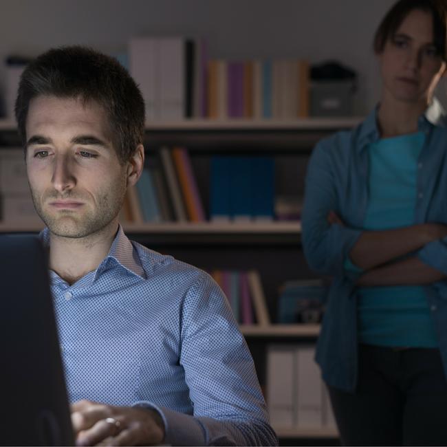 man on computer sad wife behind