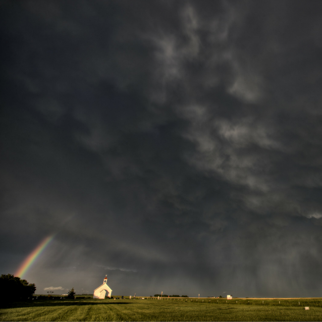 church with dark cloud and rainbow over it