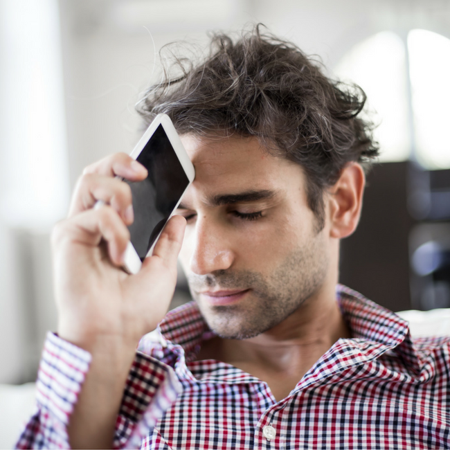 man holding phone to forehead
