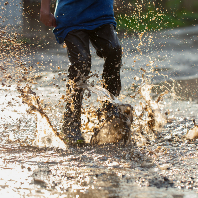 kid jumping in mud