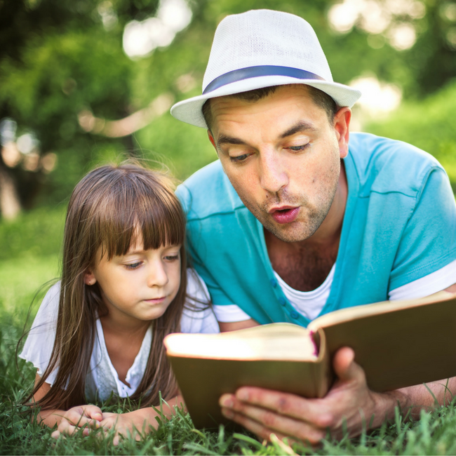 dad reading to daughter outside