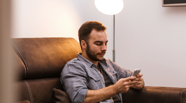 man texting on couch