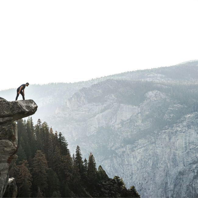 man looking off the edge of a cliff