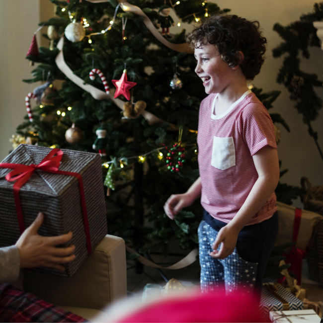 parent handing kid a Christmas present