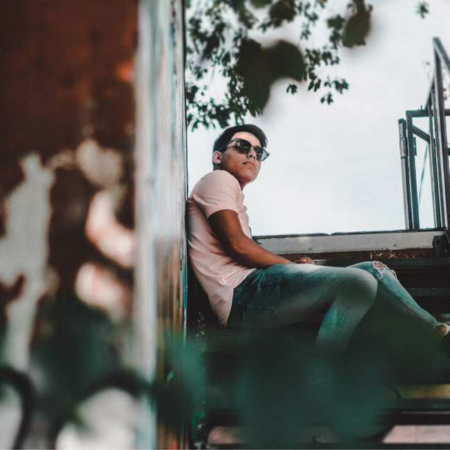 teenage boy sitting on outdoor stairs