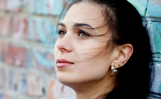 brunette woman sitting next to wall looks into distance