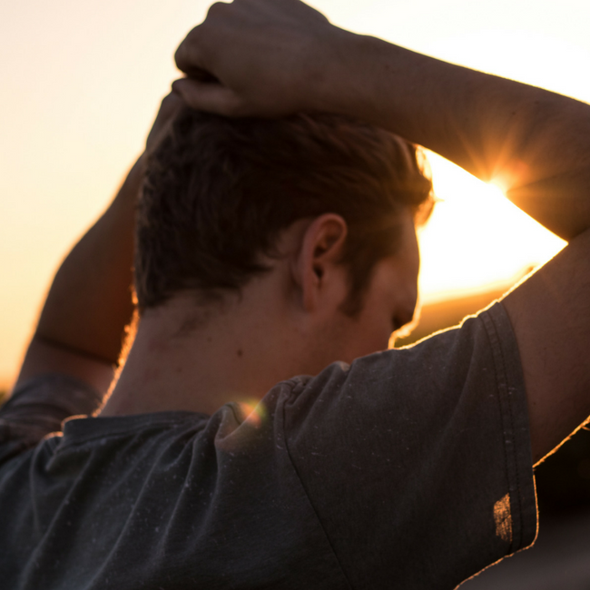 man looking at sun with hands above his head