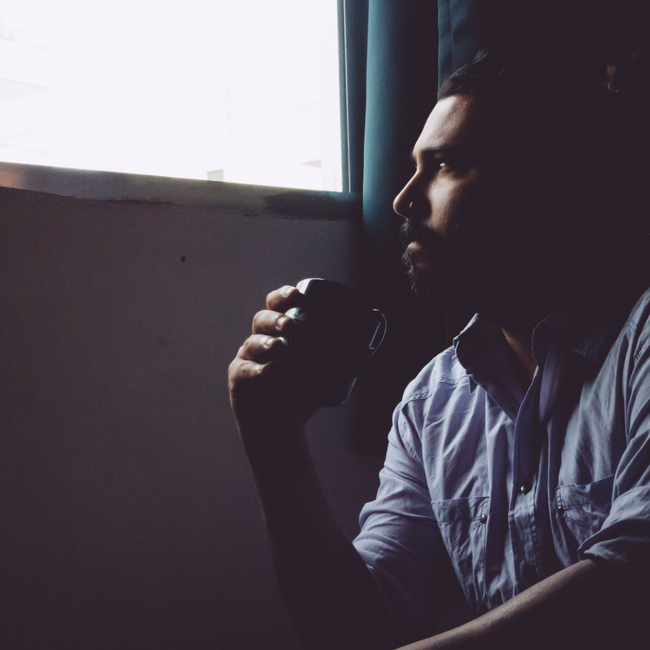 man looking out window with cup of coffee
