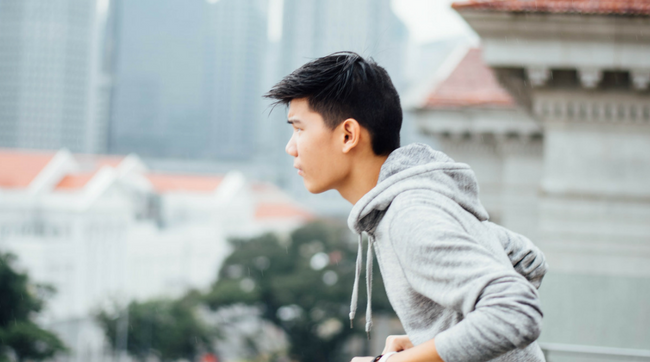 young asian man looking over balcony