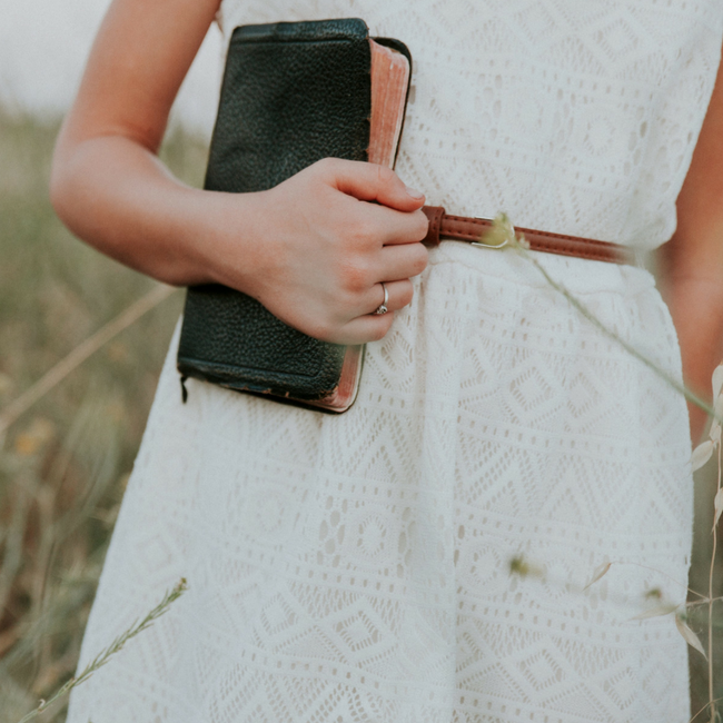 girl holding bible in white dress