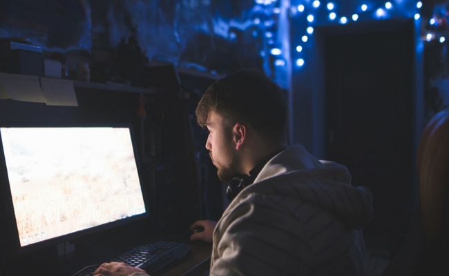 man playing computer games in dark room