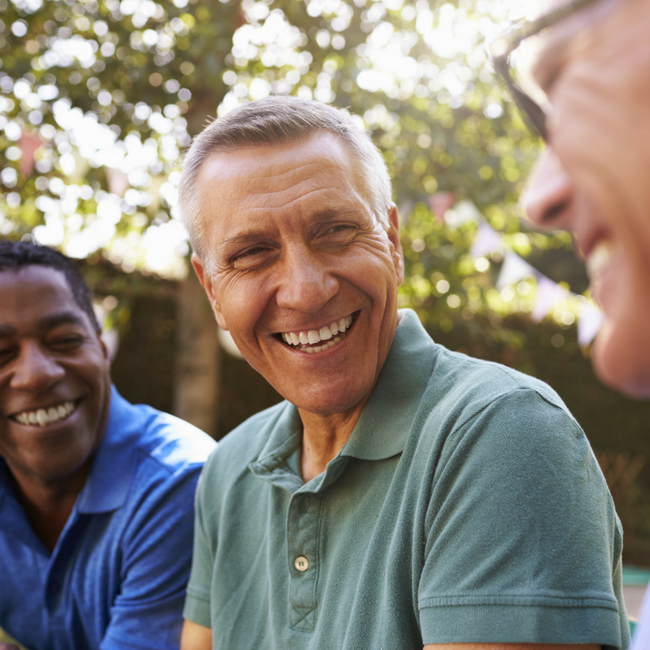three middle age men laughing together outside