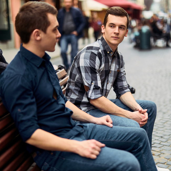two young guy friends talking on bench outside