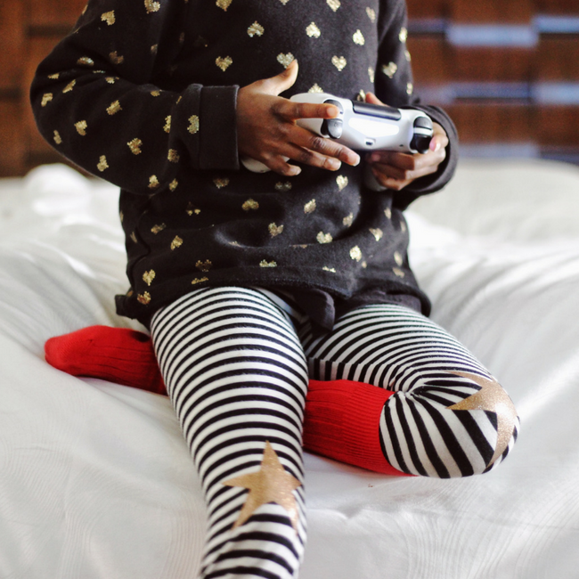 young child playing video games on bed