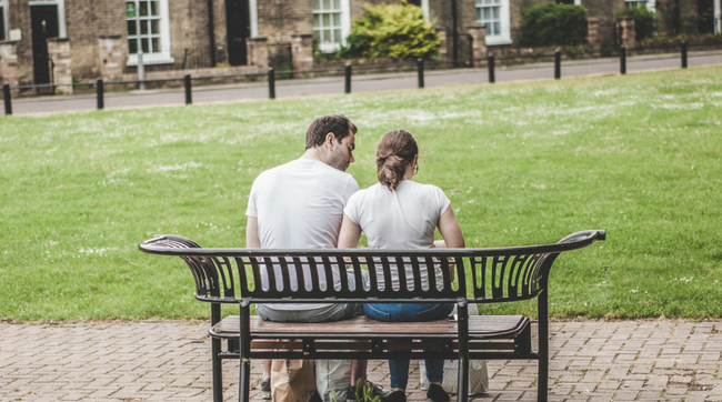 couple talking on outdoor bench