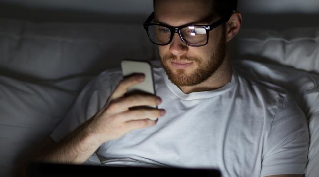 man looking at cell phone in dark bedroom