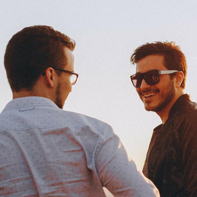 two millennial males talking outside