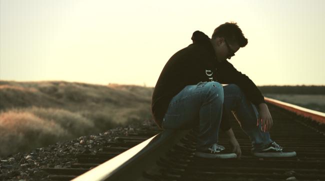 young man sitting on train tracks thinking