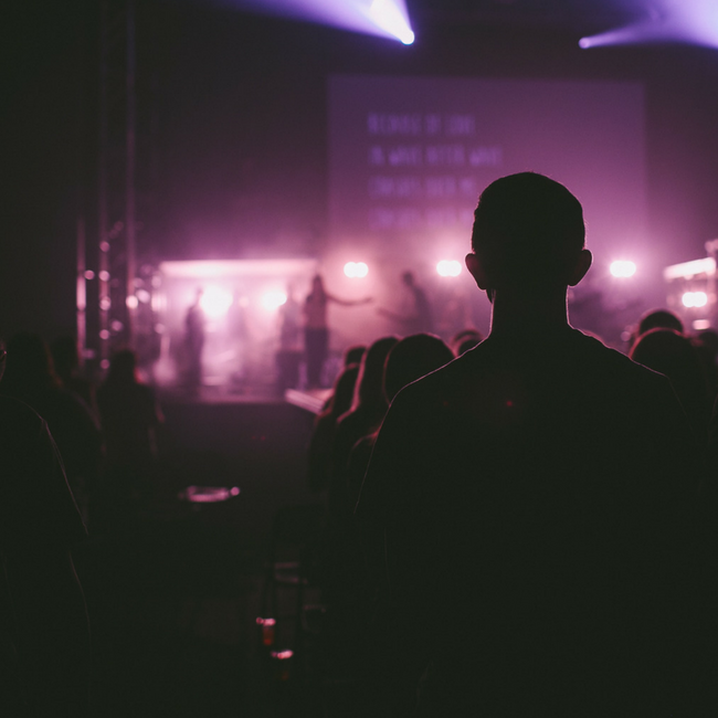 man standing at back of worship service