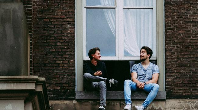 two friends talking on roof by window