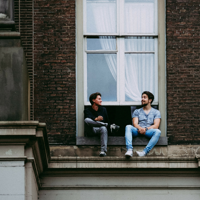 two friends talking on roof by window