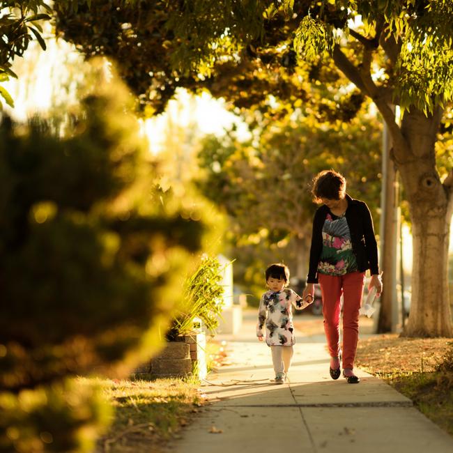 grandma and young granddaughter walking on sidewalk