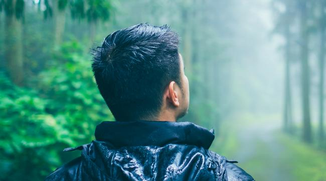 man walking on misty forest trail