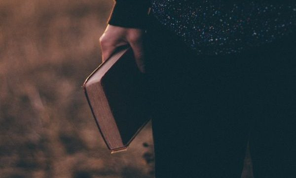 man holding bible by his side