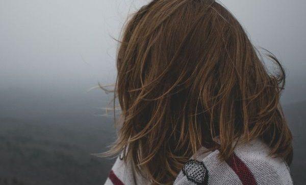 woman looking away toward fog