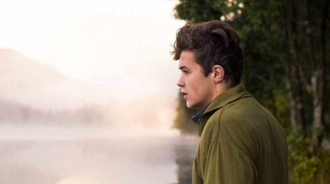 young man looking over foggy pond